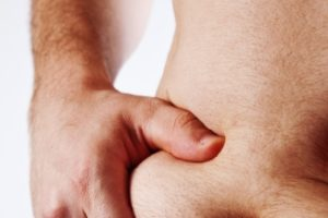 Man pinching stomach fat