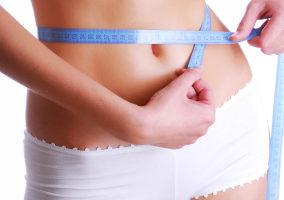 Woman measuring beauty slim waist. Health eating concept